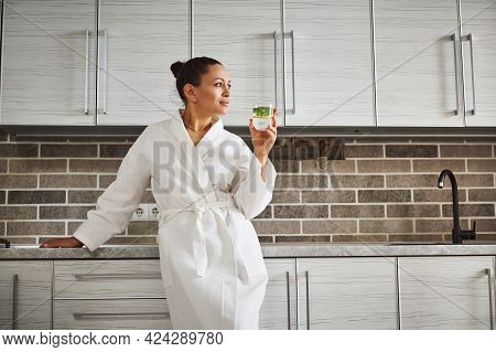 A Beautiful Woman In A White Waffle Robe Is Leaning On The Kitchen Countertop And Looking Away, Drin