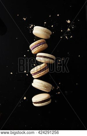 Assorted French Macarons And Crumbs On A Black Surface