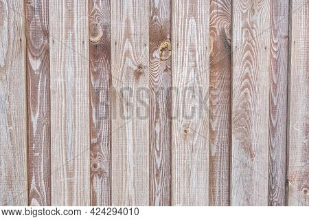 Fragment Of A Wooden Fence Made Of Pine Boards. The Tinted Surface Has A Pronounced Wood Grain. Head