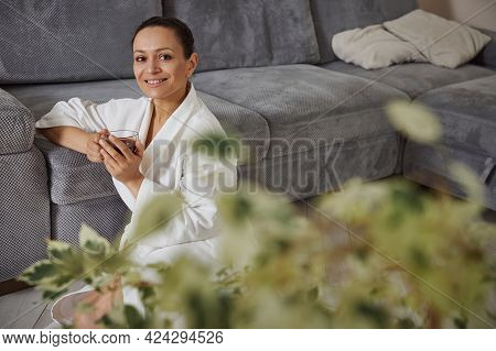 Attractive Mixed Race Woman With Cup Of Coffee In Her Hands, Leans On A Sofa While Sitting On The Fl