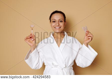 Middle Aged Woman With Beautiful Smile In White Waffle Bathrobe Posing With Gua Sha And Jade Roller