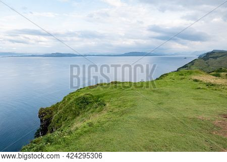Scottish Shoreline With Green Hills Near Staffin City At Isle Of Skye With Green Pastures For Sheep