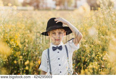 A Little Boy In A Hat In An Oilseed Rape Field. Rural Landscape