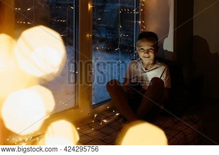 Portrait Of A Boy With A Phone In His Hands At Night At Home. Child On The Windowsill At Christmas E