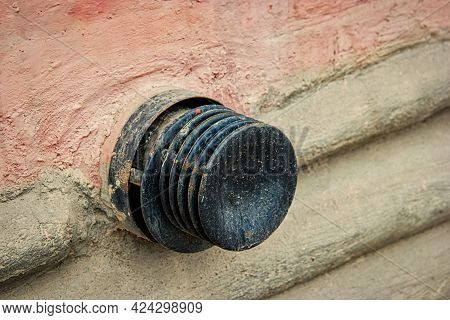 Ventilation Device. Air Vent Valve, Vent Shall - Black Metal Pipe Head Mounted On Brown Concrete Wal