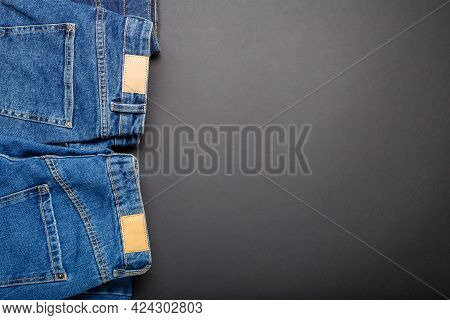 Classic Blue Jeans. Casual Pants Clothing Blue Jeans With Brown Blank Leather Labels On Black Backgr