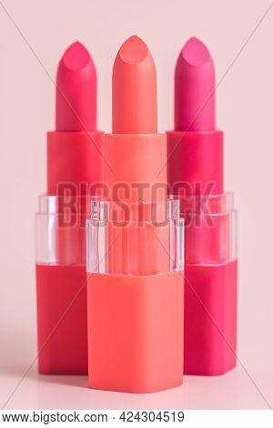 Set Of Three Color Lipsticks. Wine Lipstick, Pink Lipstick And Orange Lipstick In Colourful Lid On A