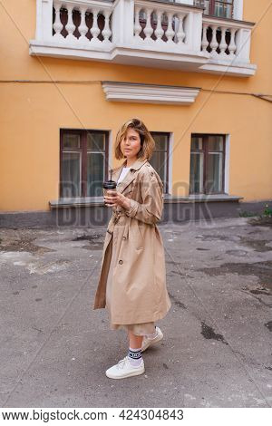 Young Millennial Woman With Wild Hair Dressed In An Autumn Coat Walking With A Cup Of Coffee To Go N