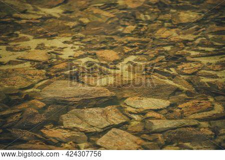Beautiful Fragment Of Orange Stony Bottom Of Mountain Lake With Transparent Water. Colorful Minimal