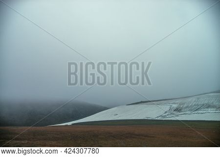 Atmospheric Minimalist Mountain Landscape With Small Glacier On Rocky Hill Slope Inside Low Cloud. M