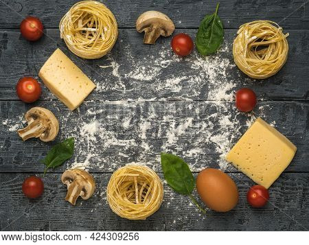 Ingredients For Making Pasta With Mushrooms And Tomatoes On A Wooden Background. Space For The Text.