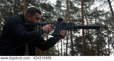 Man with KRISS Vector 9*21 caliber submachine gun in the forest. Unformal shooting range near Kiev. April 30,2021. Kiev Region, Ukraine
