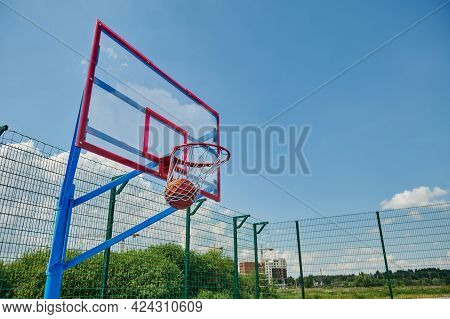 A Basketball Ball In The Basket. Scoring A Goal On The Summer Sports Court During A Basketball Game.