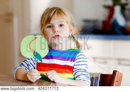 Little Toddler Girl Making Craft Apple With Paper, Colorful Pompoms And Glue During Pandemic Coronav
