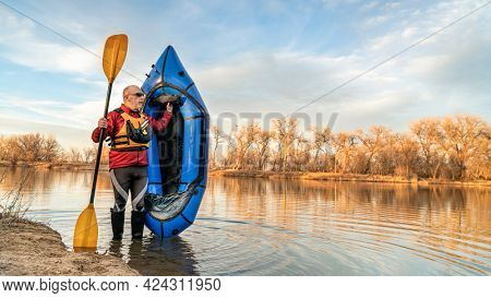 senior male paddler is standing with an inflatable packraft and paddle on a lake shore in early spring spring in northern Colorado