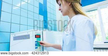pharmaceutical factory woman worker operating autoclave for medicine drug steam sterilization at pharmacy industry manufacture factory, toned photo