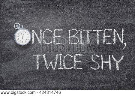 Once Bitten, Twice Shy Saying Written On Chalkboard With Vintage Precise Stopwatch
