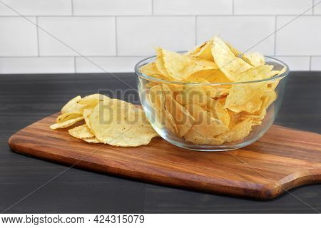 Potato Chips In A Glass Bowl On A Table In A Close Up Macro View.  Bowl Sitting On Cutting Board.