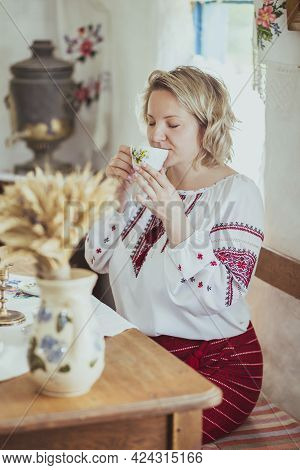 Beautiful Peasant Woman In Embroidered Clothes Drinks Tea In An Old Ukrainian Hut