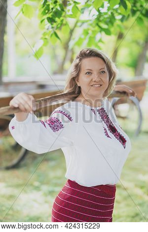 Beautiful Peasant Woman In Embroidered Clothes Walks With A Balance Beam For Buckets Of Water