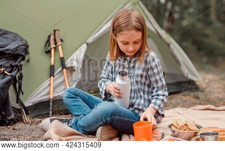 Beautiful preteen girl sitting in the forest in camping and drinking tea from the cup. Cute caucasian child making picnic with tent in the wood