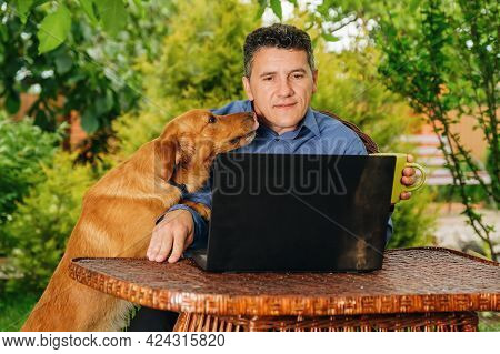 Mature Caucasian Man With His Dog Drinking Coffee, Analyzing Web Information And Reading News Via La