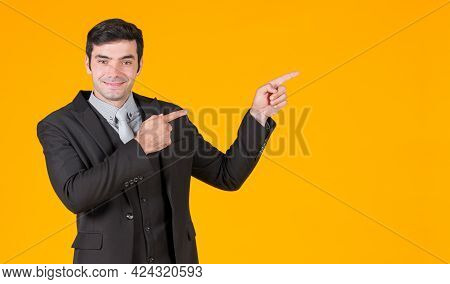 Young Caucasian Businessman In Gray Shirt And A Black Suit Pointing Both Finger In The Same Directio