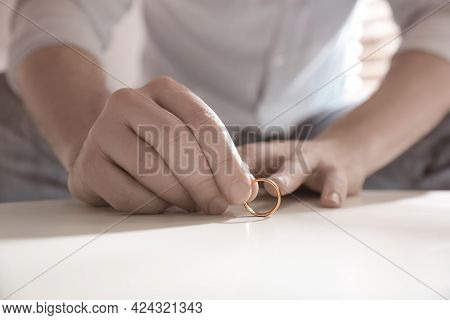 Man With Wedding Ring At Table Indoors, Closeup. Cheating And Breakup
