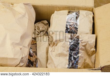 Pet Treats In Brown Paper Bags With Window. A Cardboard Box Full Of Assorted Dried Treats. Bully Sti
