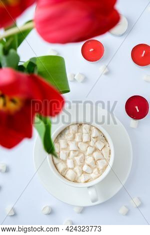 Copy Space For Text. Red Tulips Candles White Cup Of Cacao Marshmallows Morning Breakfast. Holiday B