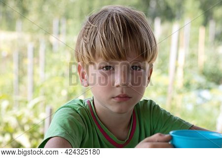 Portrait Of Blond Boy Sitting Outside On Blurry Garden Background. Ecotourism, Vacation In Country,
