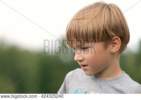 Sad 6 Years Old Caucasian Boy With Blonde Hair Outdoor Portrait At Park