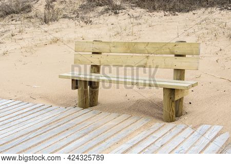 Wooden Bench And Boardwalk In The Dunes On The Shores Of The Baltic Sea.