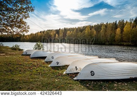 Overturned Boats Lie In A Row On The River Bank Among The Fallen Leaves In Autumn
