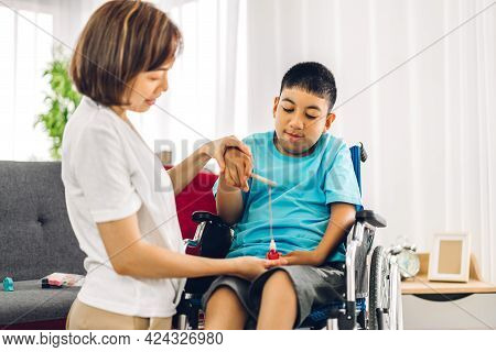 Portrait Of Asian Physiotherapist Carer Helping And Playing With Special Disabled Child Health Probl