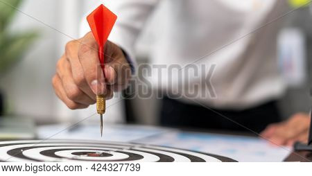 Business Men Aiming To Be Successful Business Ambitions. Man Holds A Red Darts Stabbed To The Middle