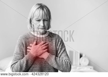 Senior Adult Elderly Women Sit On Bed With Chest Pain Suffering From Heart Attack In The Bedroom.hea
