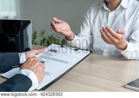 A Business Man's Hand Holding A Resume. The Management Is Taking The Exam Candidate Job Interview.