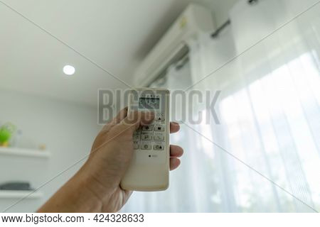 Man's Hand Off The Air Conditioner By Holding The Remote Control To The Cooler System After No One I