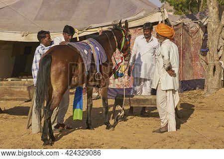 Pushkar, Rajasthan, India - November 7, 2008: Group Of Men Inspect A Horse At The Annual Pushkar Fai