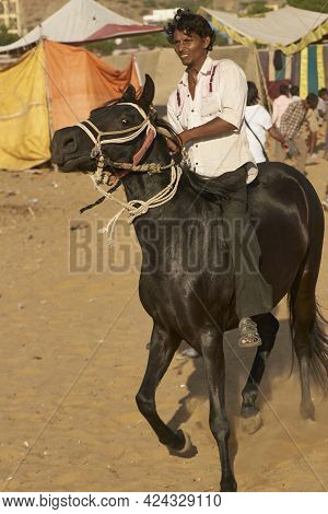 Pushkar, Rajasthan, India - November 7, 2008: Man Riding A Horse At The Annual Pushkar Fair In Rajas