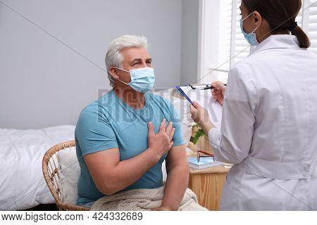Doctor Examining Senior Man With Protective Mask At Nursing Home