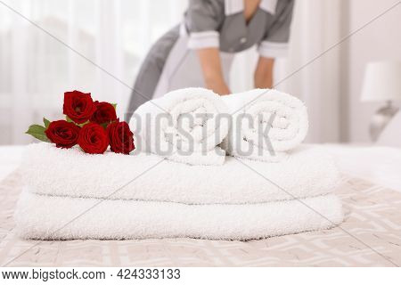 Chambermaid Making Bed In Hotel Room, Focus On Fresh Towels