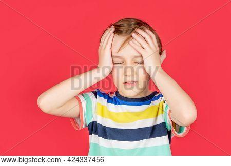 Headache Child. Suffering Migraine. Headache Because Stress. Portrait Of A Sad Boy Holding His Head