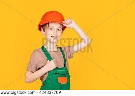 Little Builder In Helmet. Child Dressed As A Workman Builder. Little Boy Wearing Helmet. Portrait Li