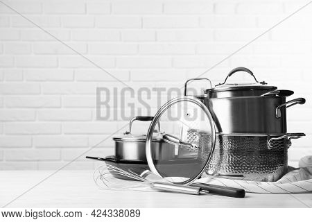Set Of Clean Kitchenware On White Table Against Brick Wall. Space For Text