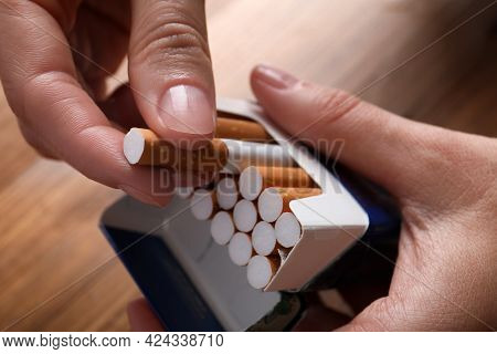 Woman Taking Cigarette Out Of Pack At Wooden Table, Closeup