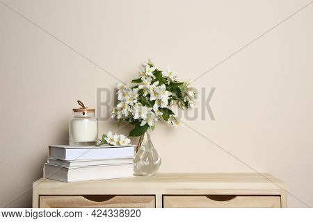 Bouquet Of Beautiful Jasmine Flowers In Glass Vase, Books And Candle On Wooden Commode Near Beige Wa
