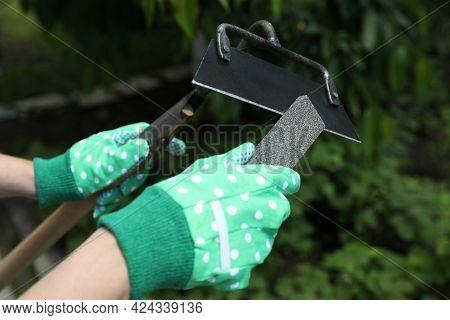 Woman Sharpening Hoe Outdoors, Closeup. Gardening Tools
