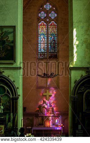 St Emilion, France - September 8, 2018: Pieta In Hues Of Purple And Red - Symbolic Reference To The
